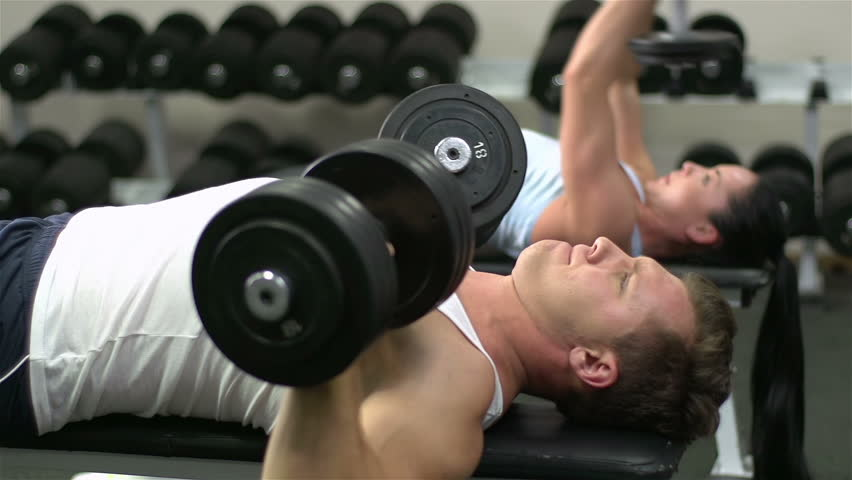 Determined athletes lying on the bench and lifting dumbbells