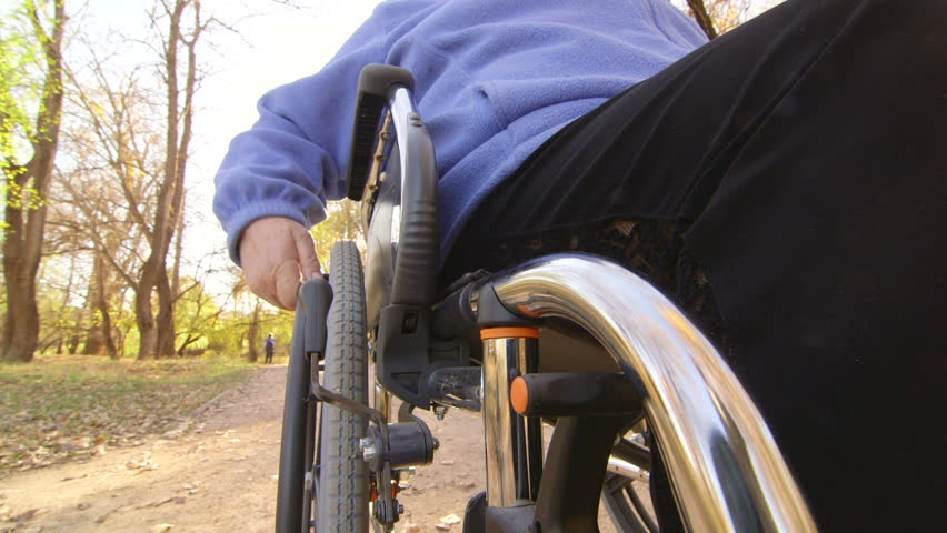 Disabled senior person turning wheels of wheelchair, camera mounted on a chair.