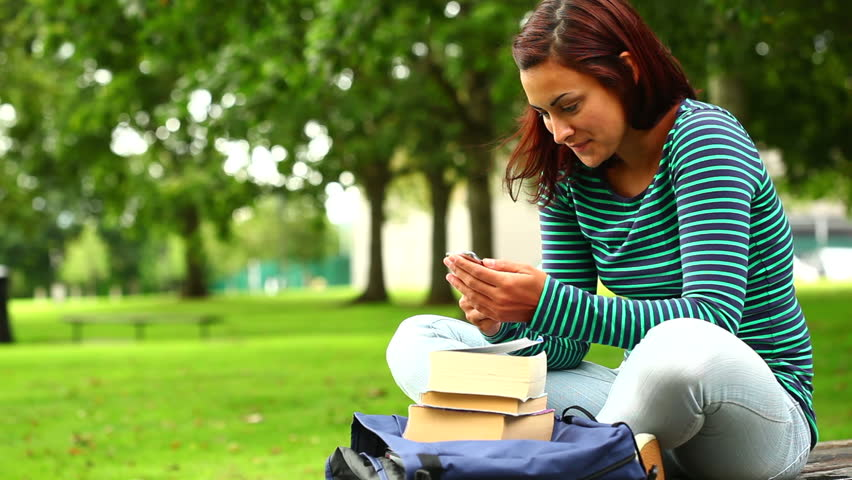 Pretty student sending a text on the grass at the university