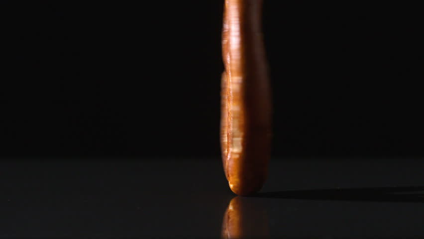 Pretzel falling and bouncing on black surface in slow motion - HD stock footage clip