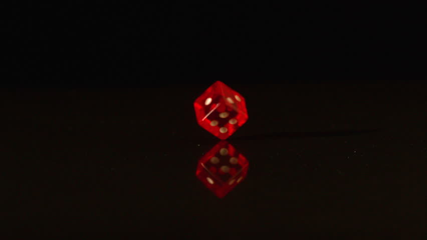 Red plastic dice revolving on black background in slow motion - HD stock video clip