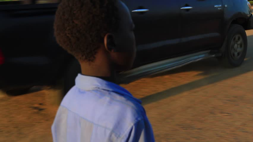 SOUTH SUDAN - CIRCA 2010: Young African boy walks down the road in the early morning - HD stock video clip