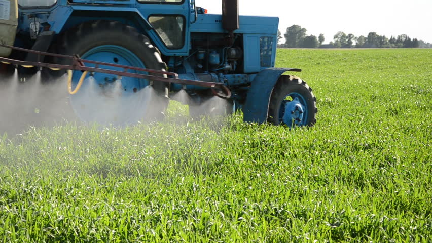 Tractor spray fertilize field with herbicide chemicals and farmer man with meter tool in agriculture field and evening sunlight.