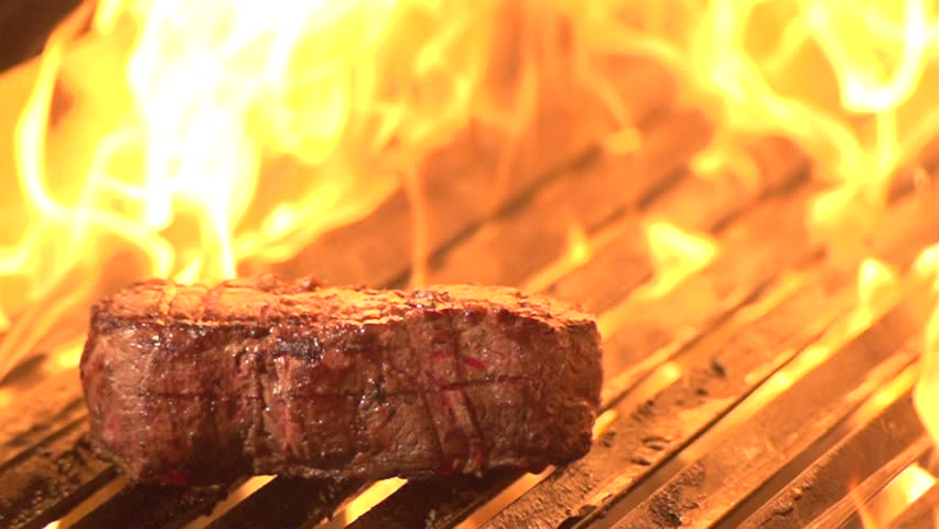 Steak on grill with flames in background