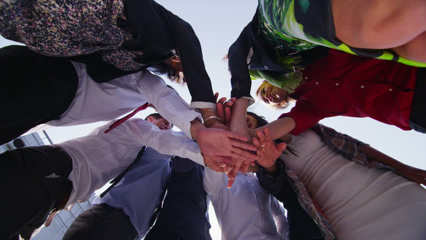 Motivational business team stand in a circle with their hands together for a team talk, outdoors in the city on a bright sunny day. In slow motion.