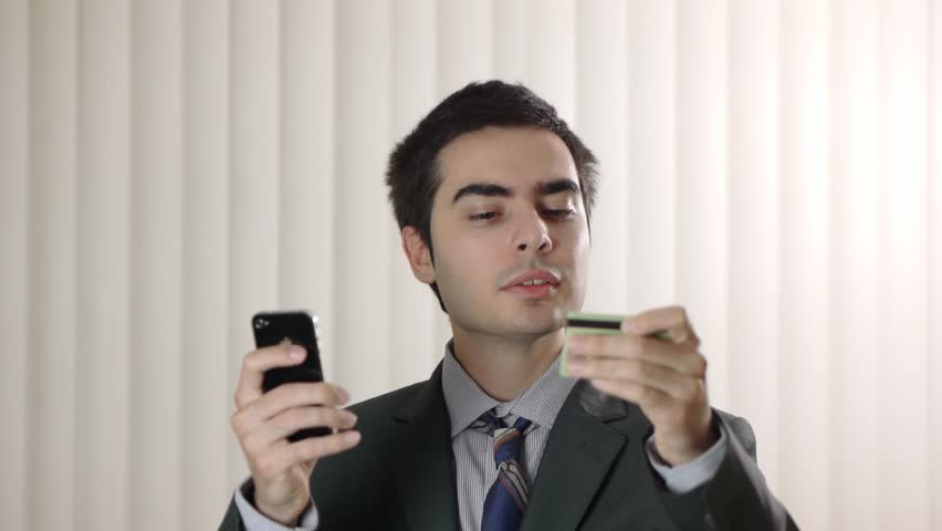 Businessman shopping with a credit card in one hand and a smartphone iPhone on