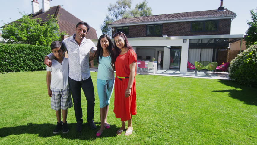 Portrait of happy young asian family, standing in the garden of their contemporary home in the summertime. In slow motion.