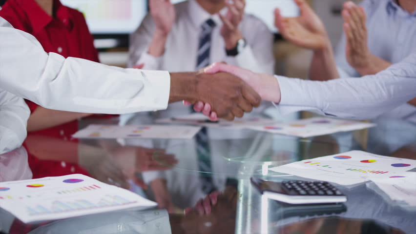 Financial business group negotiating a deal in the boardroom. When the calculations are favorable, hands reach across the table to shake hands on the deal. In slow motion.