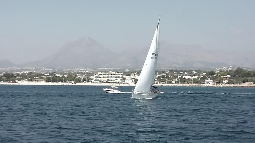 Sloop and motor boat sailing Altea coast - HD stock video clip