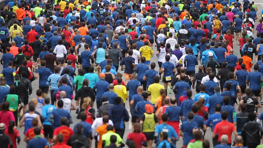 Street crowded with runners in a popular race in slow motion