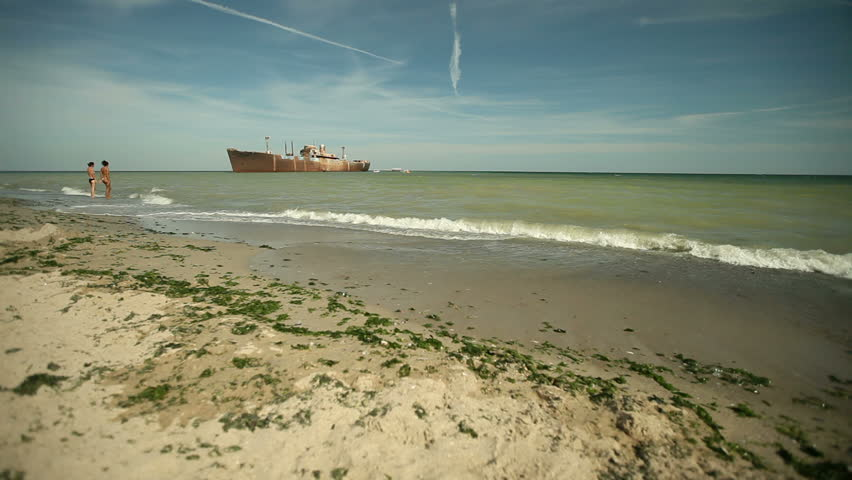 Sea waves wash beach sand. Shipwreck in background. Low wide angle view. - HD stock footage clip