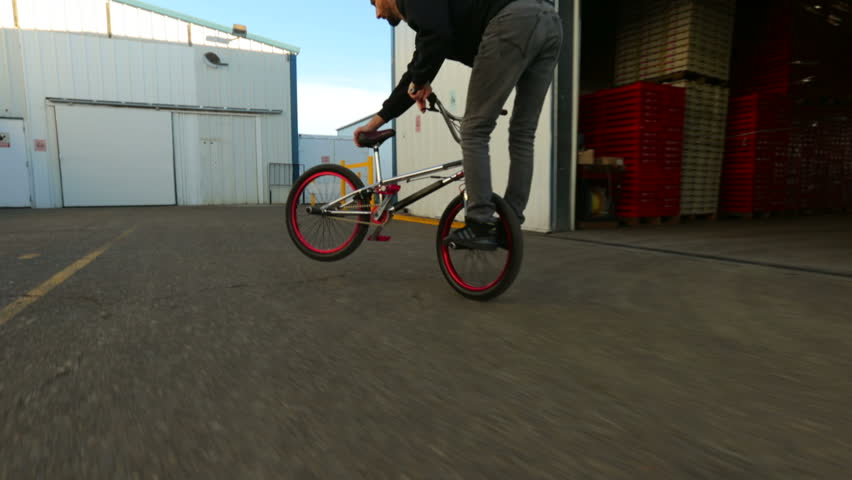 BMX rider doing tricks a commercial plant - HD stock footage clip