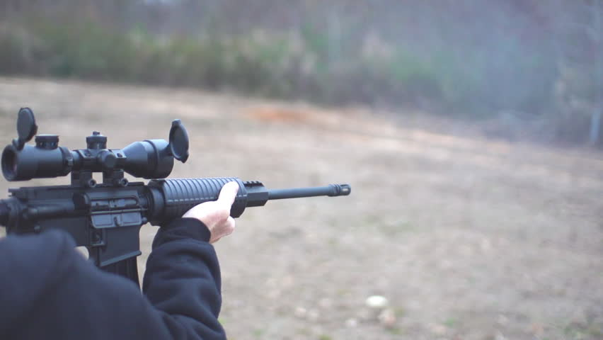 Military style Assault Rifle being fired in real time and slow motion by a man