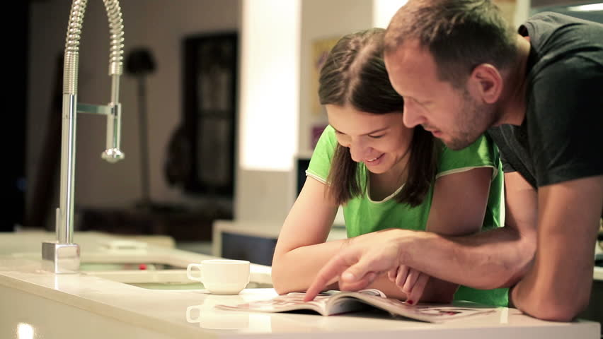 Couple in kitchen at home, chatting over magazine