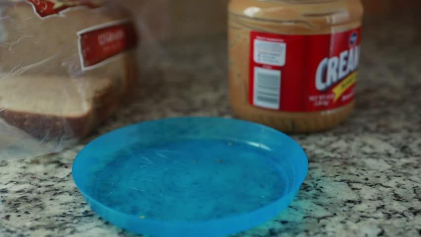 A man prepares a peanut butter sandwich time lapse