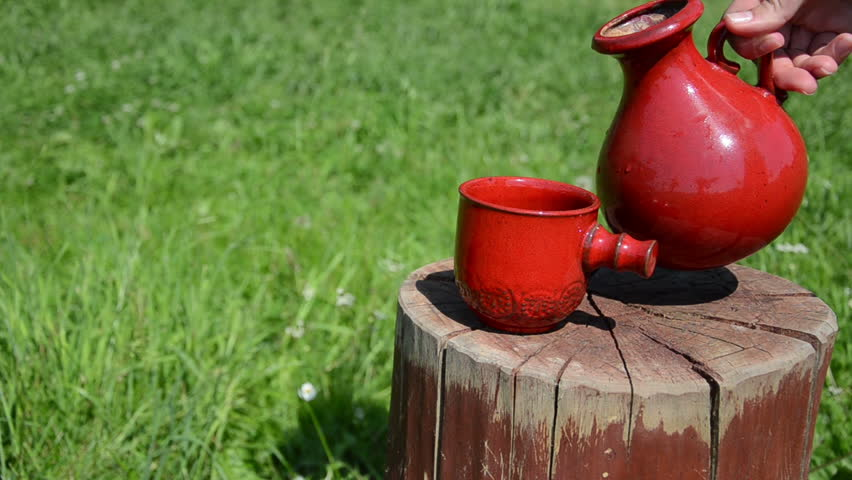 woman hand holding the clay jar and pour the water into a small pretty ornamented cup on the stump field - HD stock footage clip
