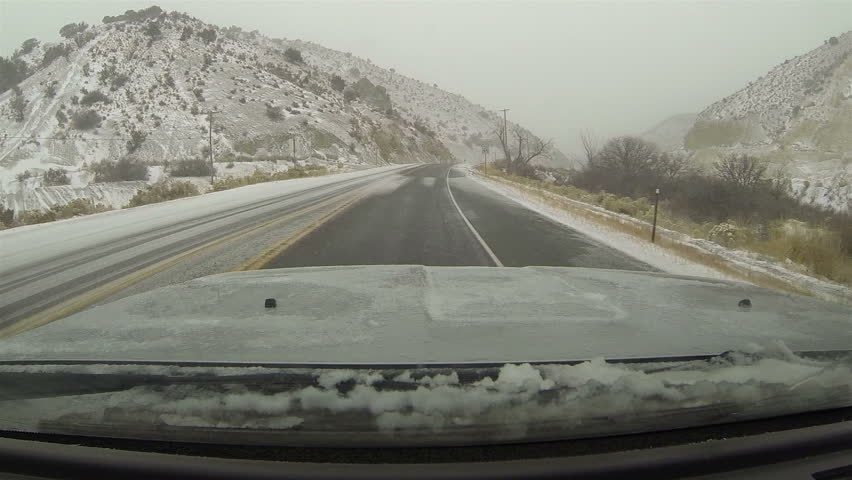 Driving mountain canyon road winter snow storm POV HD. First winter snow storm hit West and Midwest USA with extreme cold weather snow. Dangerous driving conditions on icy roads and highways. - HD stock video clip