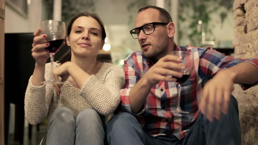 Happy attractive couple sitting on the floor and drinking red wine  - HD stock video clip