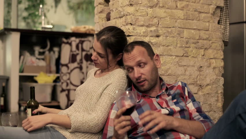 Drunk couple drinking wine and talking on the kitchen floor