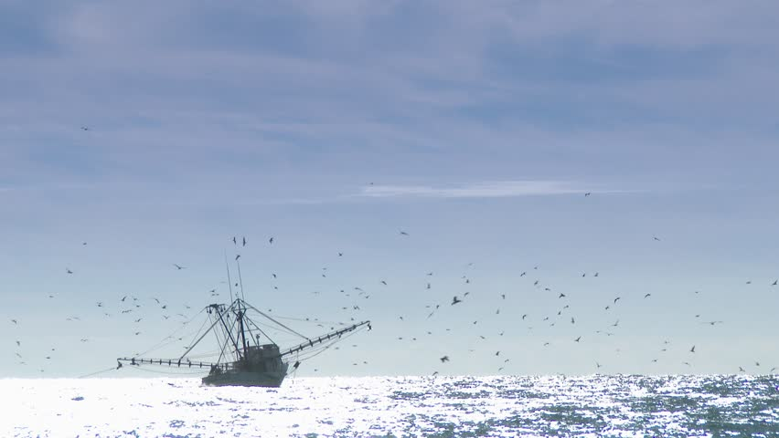 A commercial fishing boat on the horizon in the distance.  In 4K UltraHD.