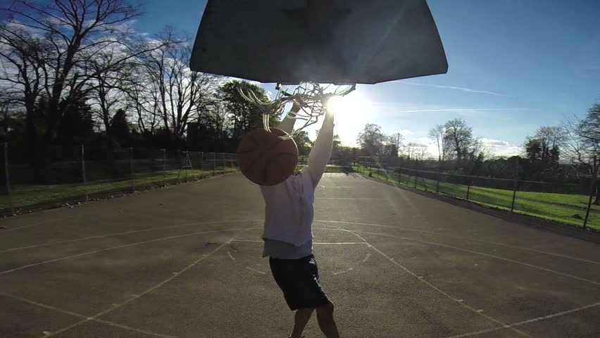Basketball player slam dunking the ball in slow motion on an outdoor basketball court - HD stock video clip