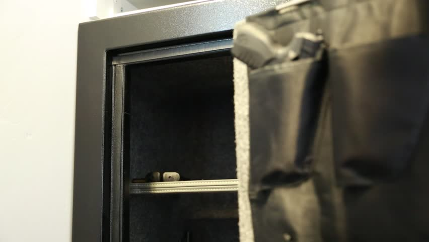 A man takes a pistol from a metal gun safe in his house