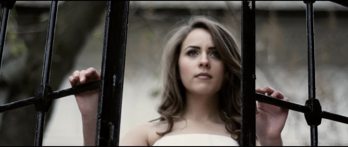 Beautiful bride in her wedding dress opening a big iron gate