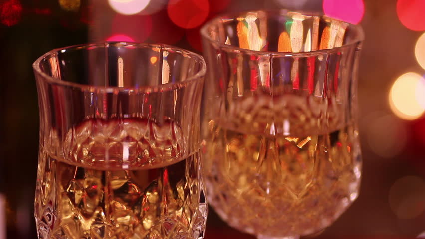 Wineglasses with white wine for celebration against festive blurry background - HD stock video clip