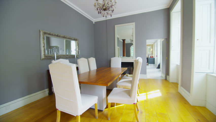 View of elegant dining room and living area in a stylish, classically designed home with large windows and lots of natural light. No people. - HD stock footage clip
