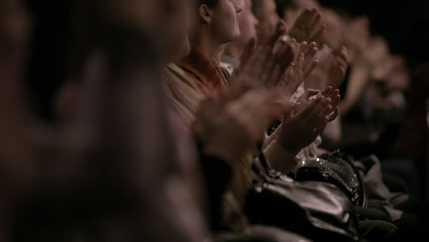 People in the theatre or in cinema auditorium applauding the perfomers