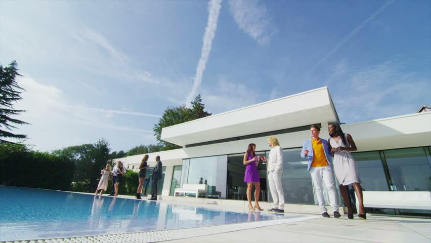 Luxury Modern Home glamorous friends enjoying drinksthe pool outside luxury