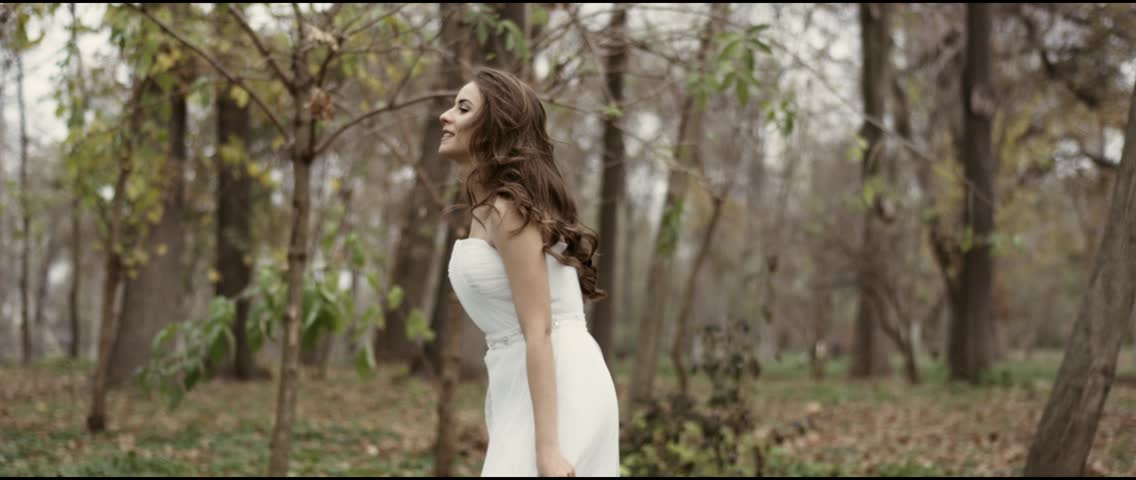 A beautiful bride in her wedding dress in park in slow motion