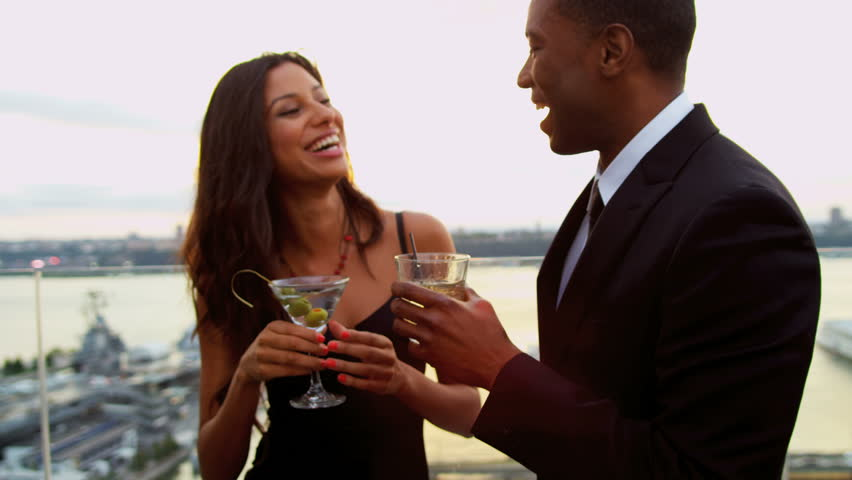 Happy multi ethnic couple taking and drinking at city roof cocktail party dressed in black shot on RED EPIC, 4K, UHD, Ultra HD resolution