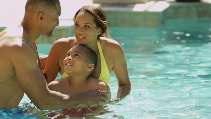 Loving ethnic parents encouraging young son learning to swim outdoor swimming pool slow motion shot on RED EPIC, 4K, UHD, Ultra HD resolution - 4K stock footage clip