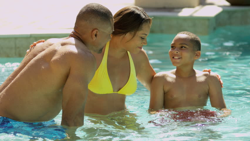 Young African American family spending time together outdoors home swimming pool shot on RED EPIC, 4K, UHD, Ultra HD resolution - 4K stock footage clip