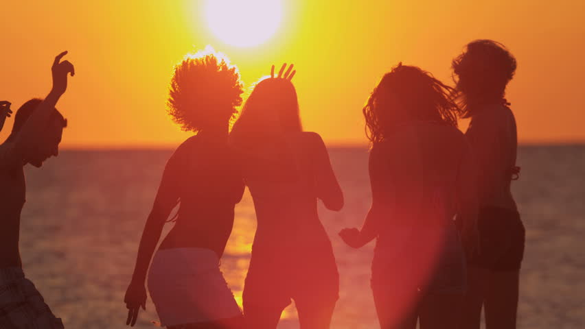 Multi ethnic male female young friends enjoying freedom college break dancing sunset coastal beach shot on RED EPIC, 4K, UHD, Ultra HD resolution