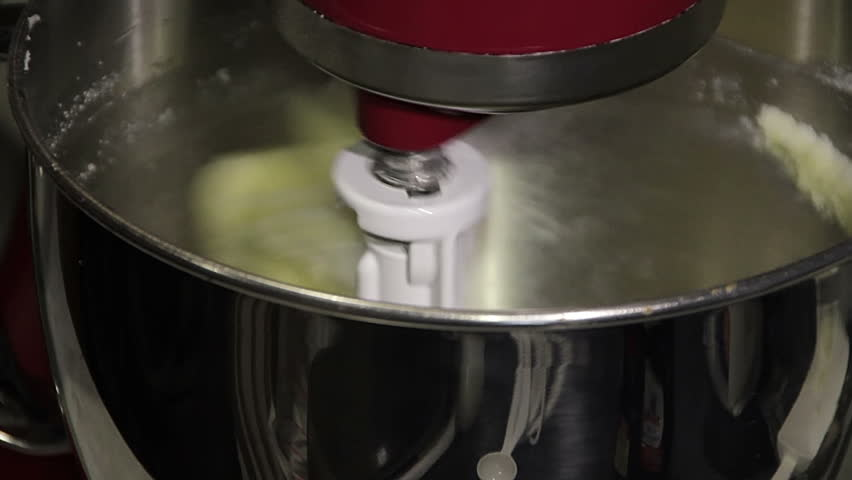 A close up of eggs being added to mixing cake batter. - HD stock video clip