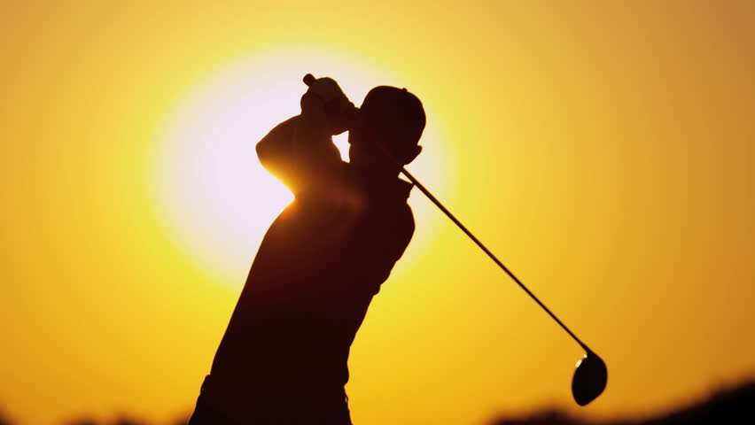 Male Caucasian golfer in sunset silhouette enjoying vacation luxury resort using driver to tee off golf course fairway slow motion shot on RED EPIC, 4K, UHD, Ultra HD resolution