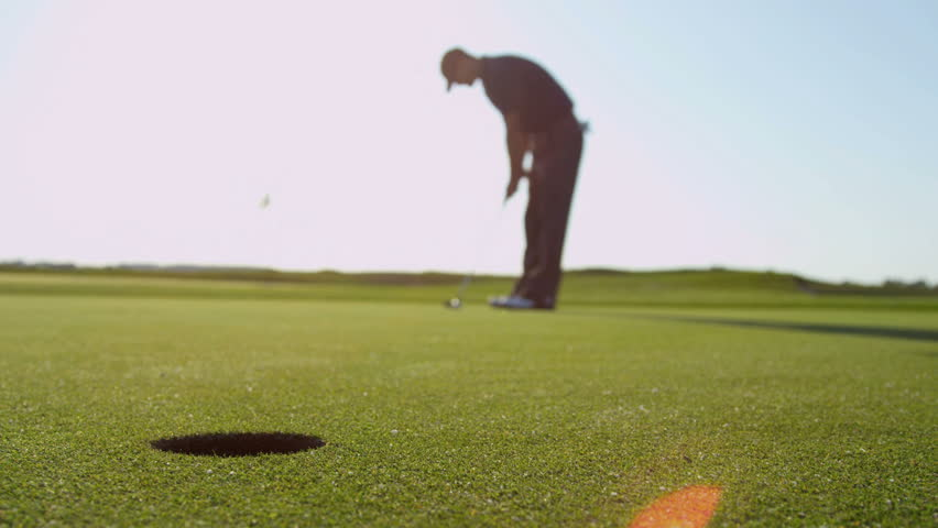 Florida - May 2013: Weekend male playing golf hitting ball on green with putter ball going wide of hole shot on RED EPIC, 4K, UHD, Ultra HD resolution - 4K stock footage clip