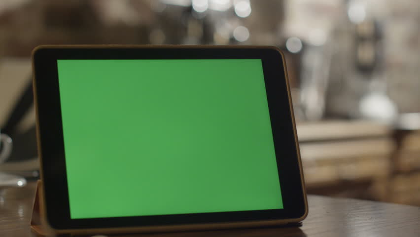Tablet with Green Screen Staying on a Table. Shot on RED Digital Cinema Camera in 4K, so you can easily crop, rotate and zoom. Great for presentation and mockups. Easy to tracking and keying.