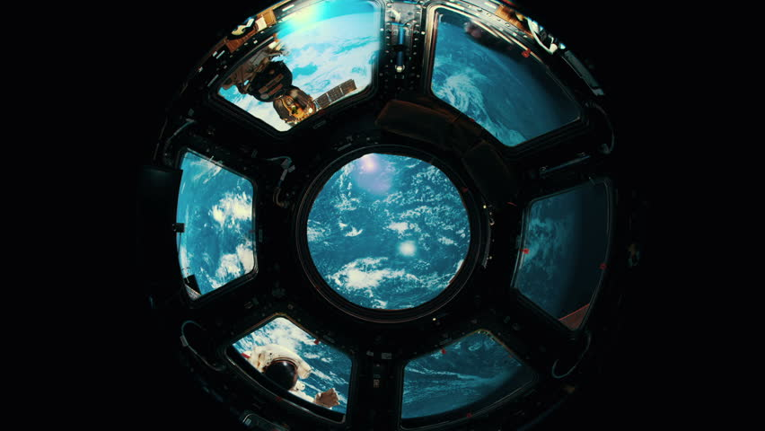 Astronaut waves to other astronauts through space station window.