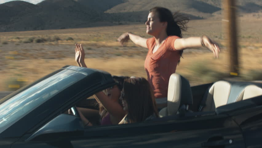 Teen Girl Stands In A Convertible And Dances On A Desert Road Trip