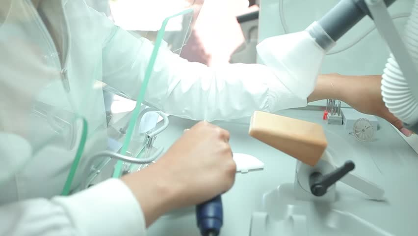 details of a denture making procedure in a dental laboratory. final stages of cast preparation before scanning. tooth separation using a precise motorised hand saw - HD stock footage clip