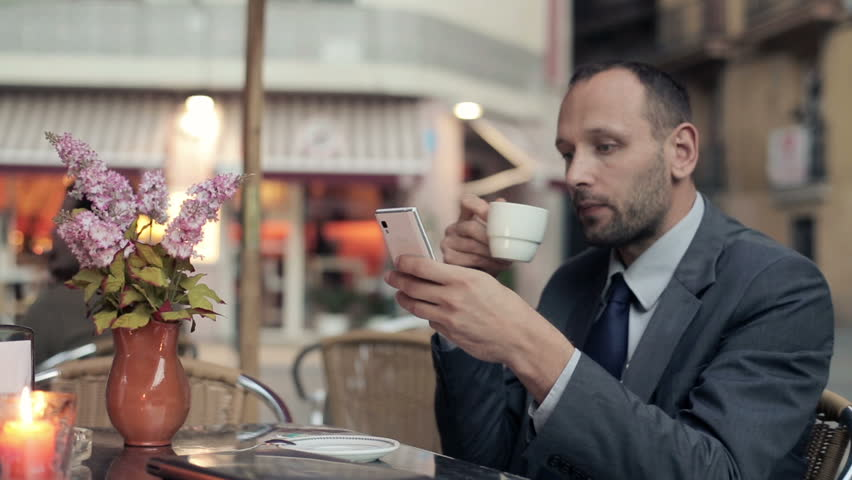 Young businessman with smartphone drinking coffee at cafe