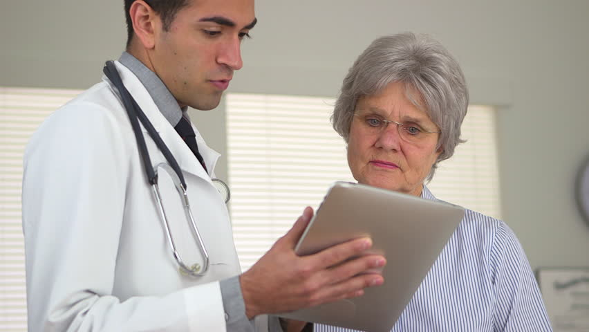 Hispanic doctor talking to mature woman with tablet