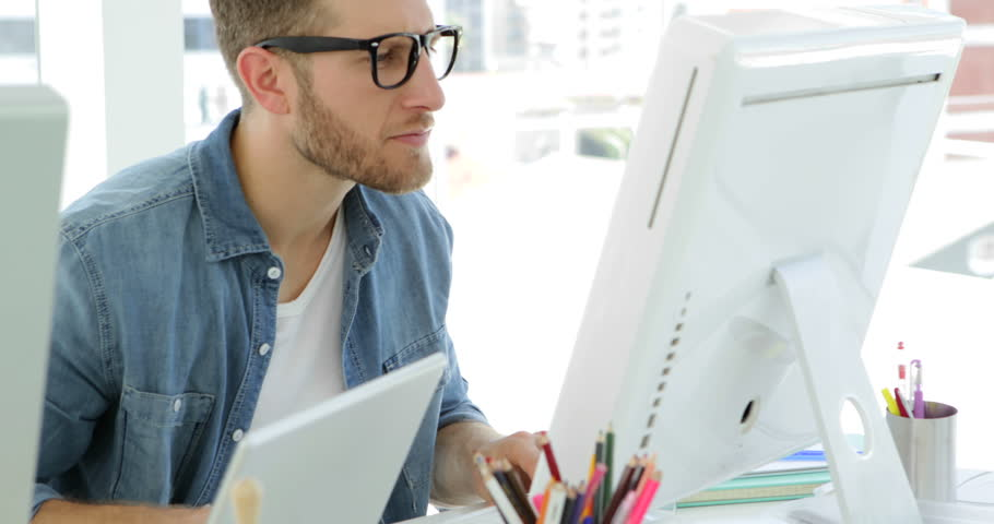 Young businessman working concentrated at his desk in the office