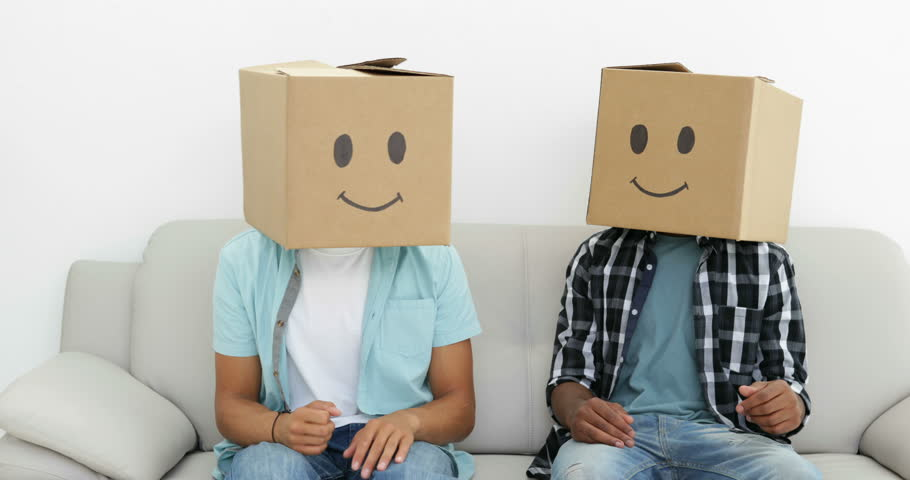 Silly employees with boxes on their heads giving thumbs up in creative office