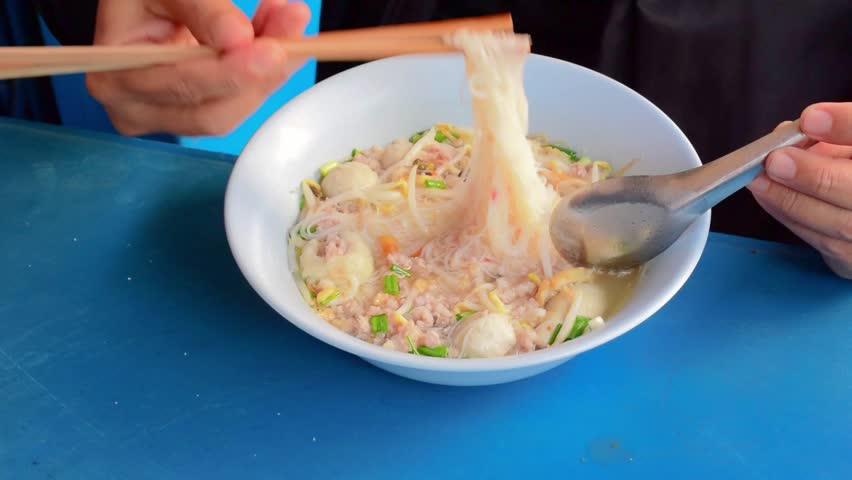 A man is eating Thai noodle with seasoning pork. It's a native Thai cuisine in Thailand.  - HD stock video clip