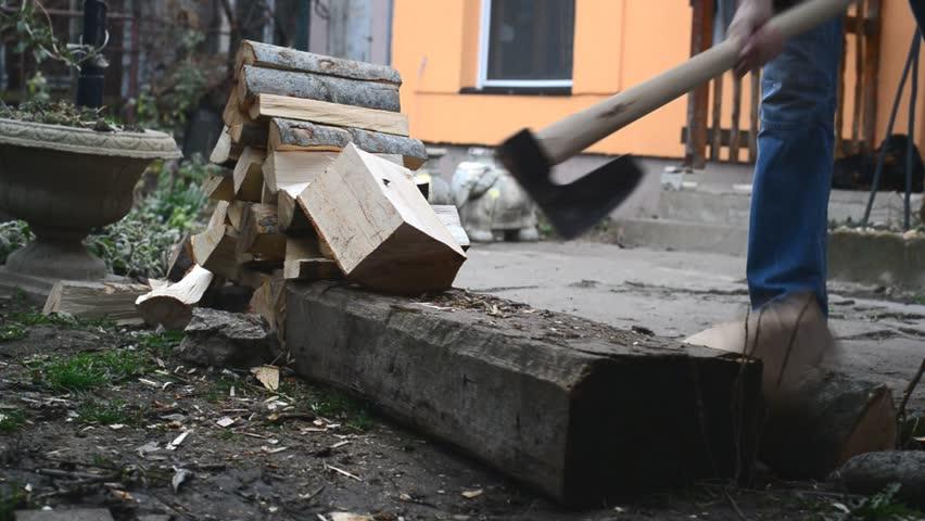 Adult man cuts wood logs with hatchet ax making firewood