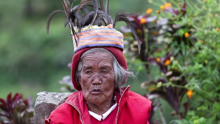 BANAUE - JANUARY 24 : Unknown old ifugao woman in national dress next to rice terraces on Jan 24, 2014 in Banaue, Philippines. Ifugao - the people in the Philippines. Refers to the mountain peoples.